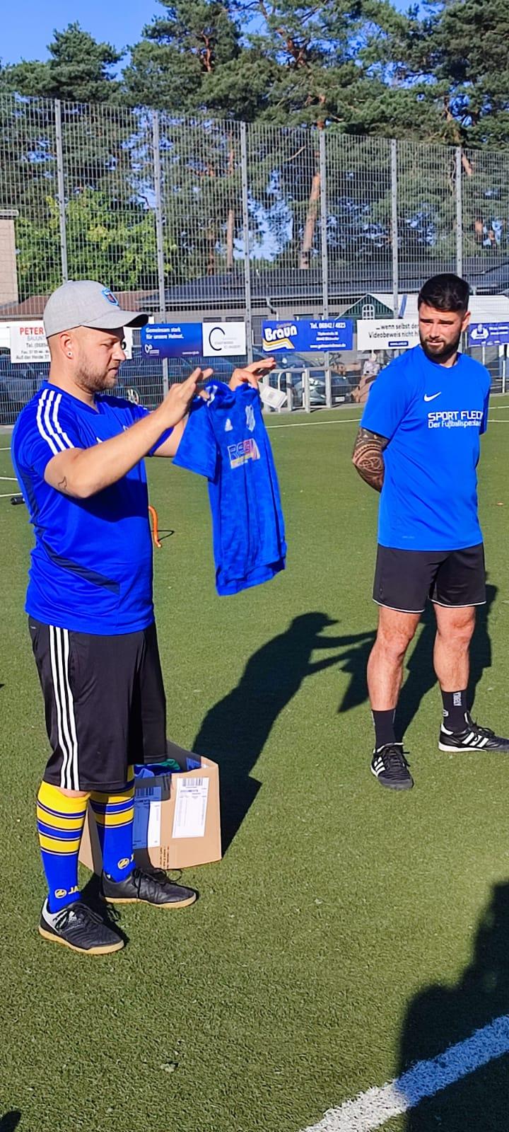 Trainer Sebastian Jung zeigt den Kids die neuen Trikots